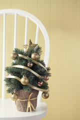A christmas tree on a windsor chair beside a yellow wainscot.