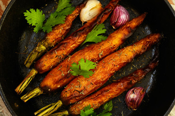 Whole baked young carrot roots with garlic and rosemary