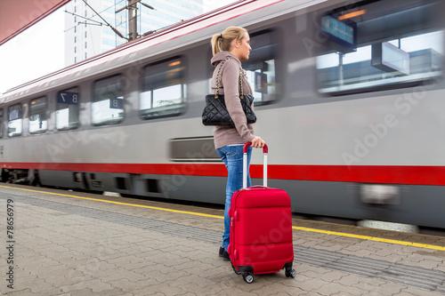 canvas print picture Frau wartet auf Zug auf Bahnhof