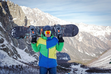 The man with the snowboard is on the background of mountains
