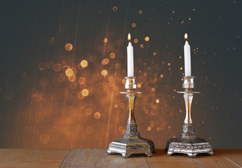two candlesticks with burning candles over wooden table and vint