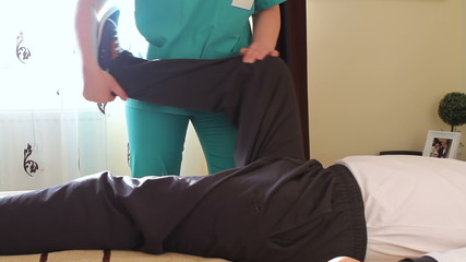 Physical therapist working rehabilitation exercises for legs