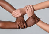 Caucasian and black African hands together against racism