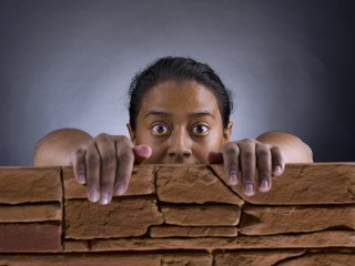 Black woman, with a look of surprise, from behind a brick wall