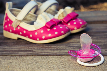 Baby shoes and a pacifier on wooden background.