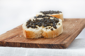 Sandwiches with black caviar lying in a row on a wooden surface