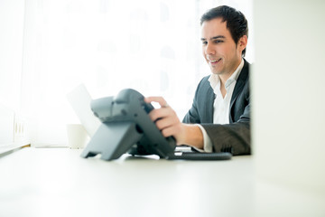 Businessman smiling in satisfaction after a call