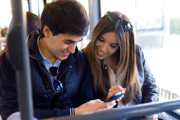 Young couple using mobile phone at bus.