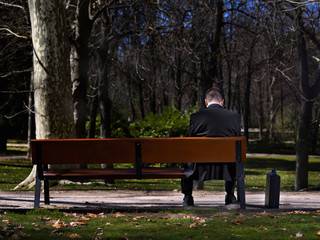 Businessman sat in a bench, looking towards to down
