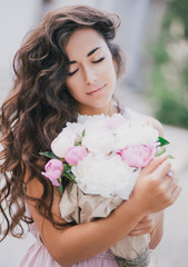 Young beautiful woman posing with a bouquet of peonies