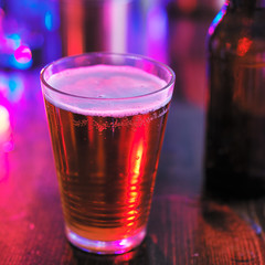 glass of beer in colorful night club or bar