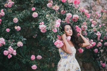Beautiful young woman posing near roses in a garden