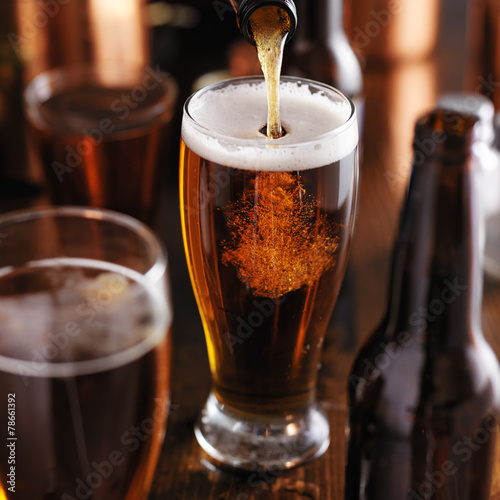 pourng beer from bottle into glass at bar Poster
