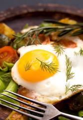 Closeup fried egg and vegetables with fork