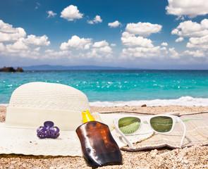 Sunglasses , sunsunhat, suncream on beach.