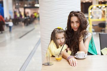 Mom and daughter drink coffee and juice in a cafe supermarket.