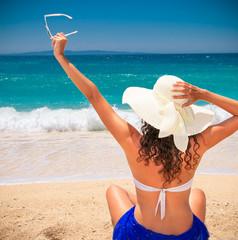 Beautiful woman in sunhat  enjoying on beach.
