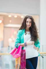 Young woman with shopping bags on the background of shop windows