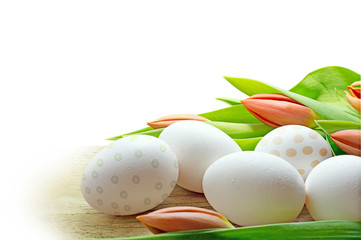 white eggs and orange tulips, corner background for easter