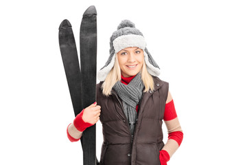 Young girl in winter clothes holding skis