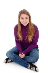 Adorable blonde teenager looking at camera sitting on floor