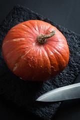 Ripe Pumpkin and a Sharp Blade on a Black Stone Plate