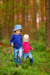 Two adorable little sisters hiking in a forest