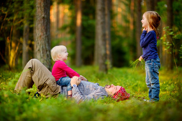 Young father and his little daughters in forest