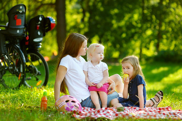 Young mother and her daughters picnicking