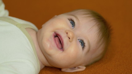 The baby lies on the bed look and smile. Close-up portrait view