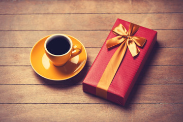 Cup of coffee and gift box on a wooden table.
