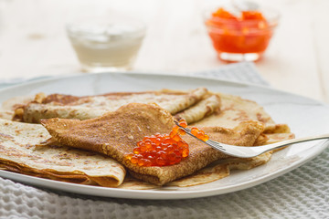 Traditional Russian breakfast: pancakes and red caviar on a plat