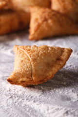 Indian samosa close-up on a table with flour. vertical