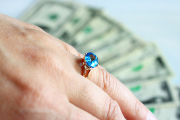 Hand with topaz on the finger and dollars