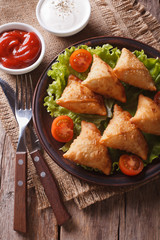 Indian samosa on a plate with sauce closeup, vertical top view