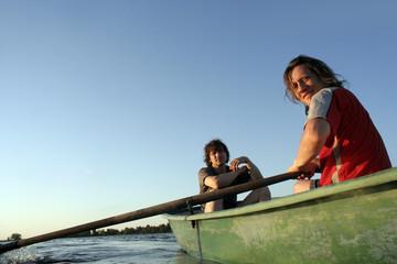 Двое мужчин в лодке гребут на закате