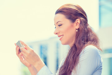 young woman in blue shirt holding using smart phone