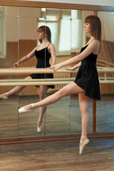 girl practicing dance holding Barre