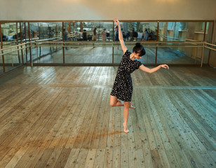 Slim girl dancing in  ballroom