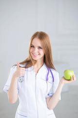 Doctor holding a green apple. Concept of healthy food.