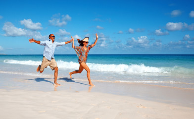 Happy couple running on the beach.