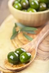 Aceitunas verdes y aceite de oliva en cuchara y bowl de madera