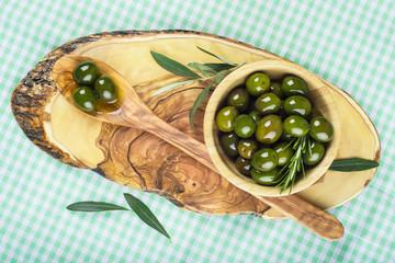 Bowl y cuchara de madera con aceitunas y aceite de oliva
