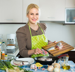 Housewife cooking fish at home