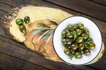 Plato de aceitunas verdes con aceite de oliva y hojas de olivo