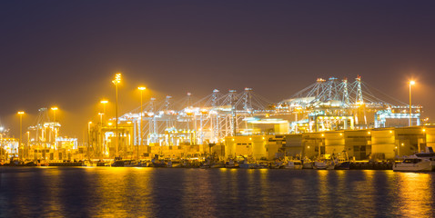 night  view of   cranes and containers in cargo seaport