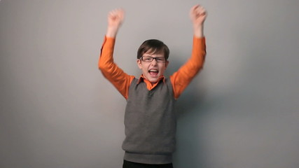 teenager boy succeeded joy waves his hands for ten years glasses