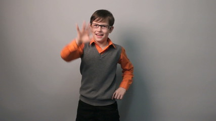 teenager boy dancing funny waving his arms in glasses ten years