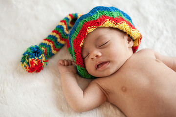 Newborn baby girl sleeping with colorful hat