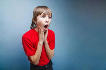 Boy, teenager, twelve years in the red shirt surprised open mout
